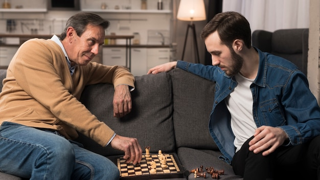 Meados de tiro pai e filho jogando xadrez na sala de estar