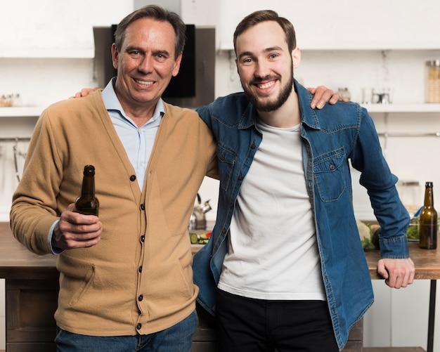 Meados de tiro pai e filho posando na cozinha