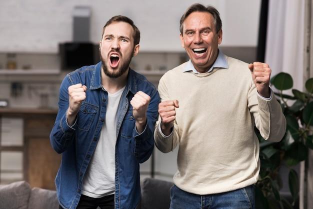 Meados de tiro pai e filho torcendo na sala de estar
