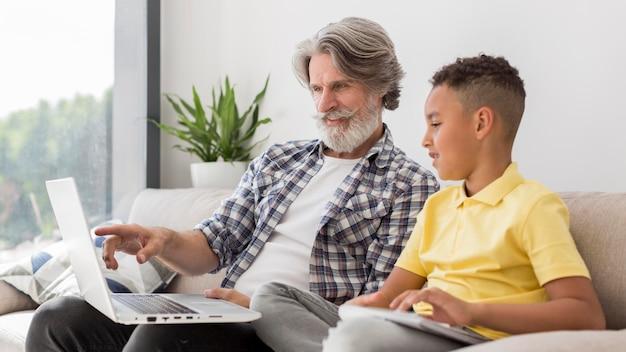 Meados de tiro professor e aluno olhando para laptop