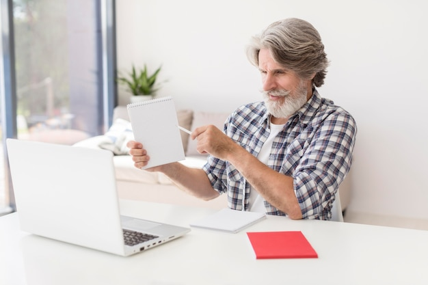 Meados de tiro professor mostrando o notebook no laptop