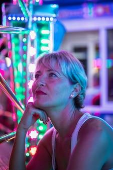 Meados envelhecida mulher pensando em lâmpadas brilhantes