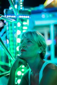 Meados idade mulher olhando lâmpadas brilhantes