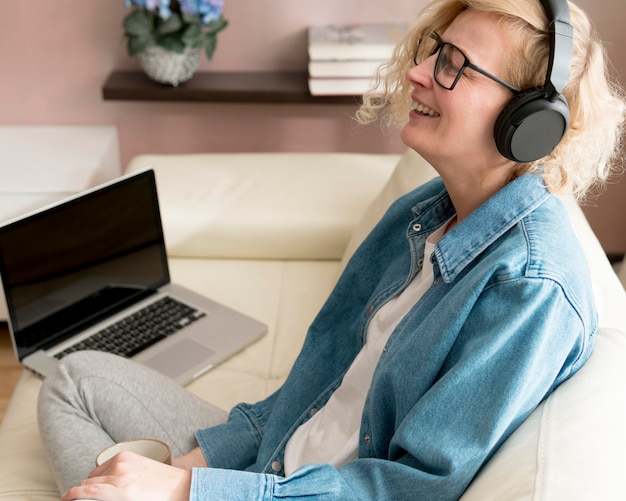 Meados tiro mulher loira ouvindo música e bebendo café