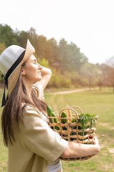 Meados tiro mulher usando chapéu e segurando a cesta com compras, olhando para longe