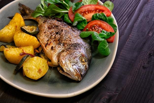 Meal.baked peixe dorado com legumes no forno em um fundo escuro.