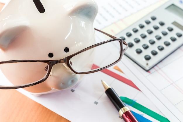 Mealheiro e calculadora no fundo de documentos de negócios