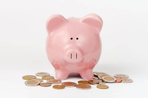 Mealheiro e euro- moedas na parede branca. conceito de economia de dinheiro.