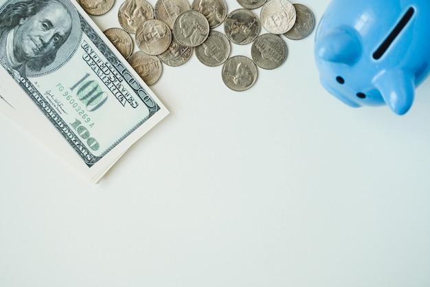 Mealheiro, moedas e pilha de notas de dólar