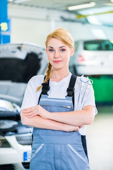 Mecânica de automóveis trabalhando em oficina de automóveis