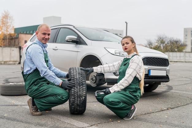 Mecânica de mulher verificando roda sobressalente perto do carro