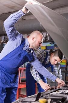 Mecânica dos carros trabalhando na carshop
