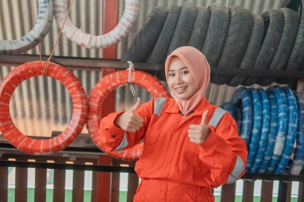 Mecânica feminina com um véu olhando para a frente com o polegar para cima em frente a um suporte de pneus em uma oficina de peças sobressalentes de motocicletas Foto Premium