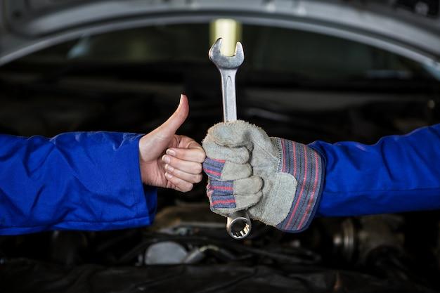 Mecânica segurando a chave inglesa e mostrando os polegares para cima