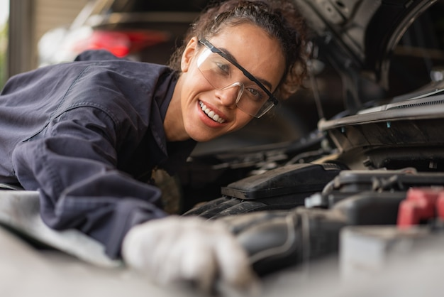 Mecânica sorrindo e trabalhando na manutenção de um carro na garagem de serviço