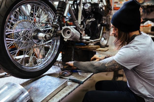 Mecânica tatuada fixação de motocicleta em oficina
