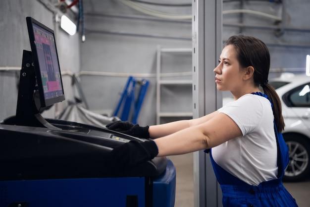 Mecânica usa um computador para trabalhar em uma oficina