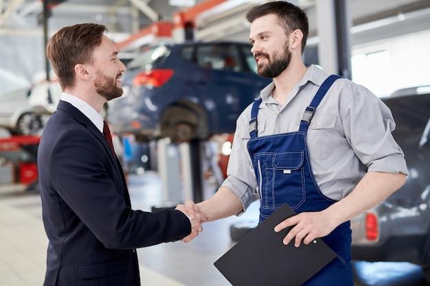 Mecânico, apertando as mãos com empresário
