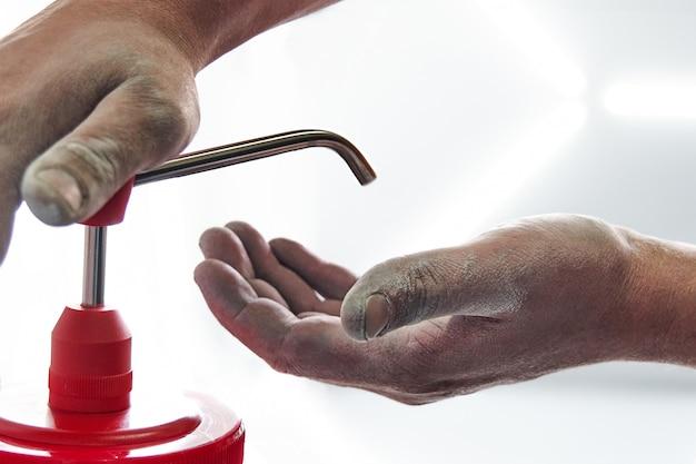 Mecânico, aplicar sabão em pó para limpar as mãos sujas depois do trabalho