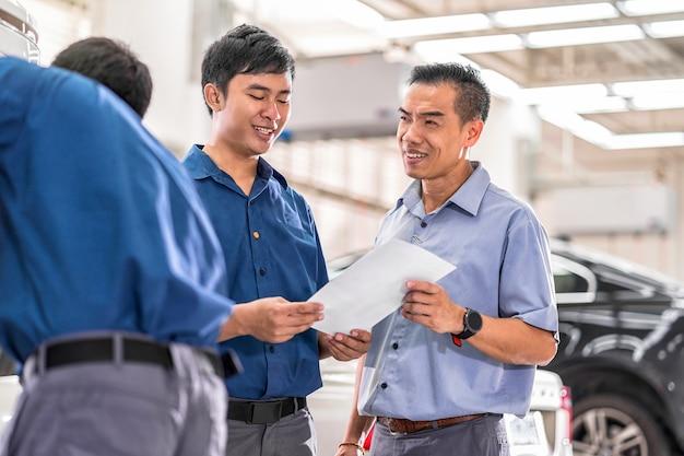 Mecânico asiático falando e mostrando trabalho ao cliente sobre o serviço de reparo