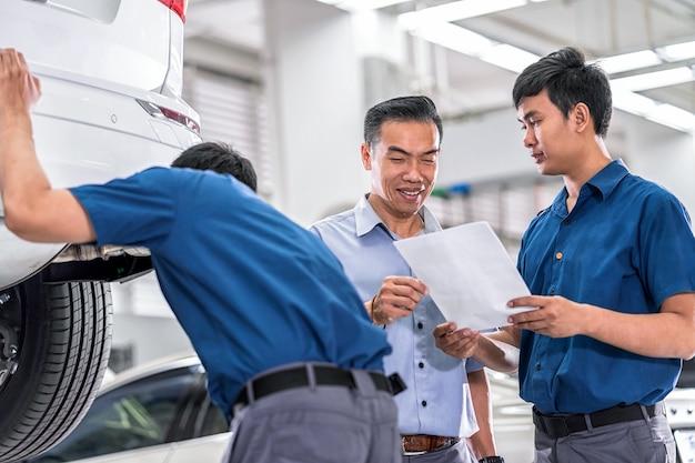 Mecânico asiático falando e mostrando trabalho ao cliente sobre serviço de reparo em serviço de manutenção