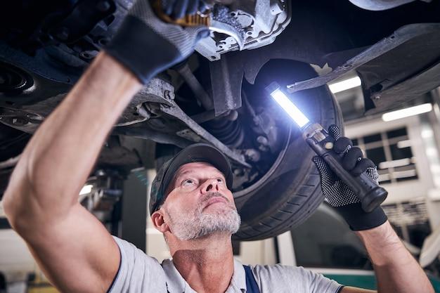 Mecânico barbudo consertando carro em posto de gasolina