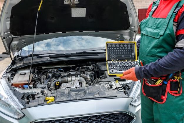 Mecânico com caixa de ferramentas posando perto de carro com capô aberto
