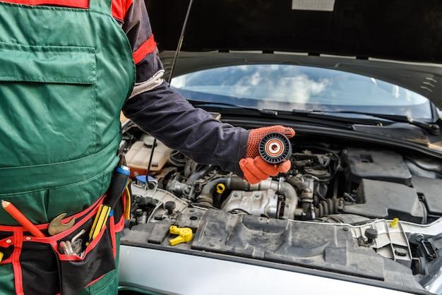 Mecânico com cinto de ferramentas mostrando o filtro do carro contra o motor do carro de perto