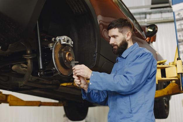 Mecânico com ferramenta. roda nas mãos de um mecânico. roupa de trabalho azul.