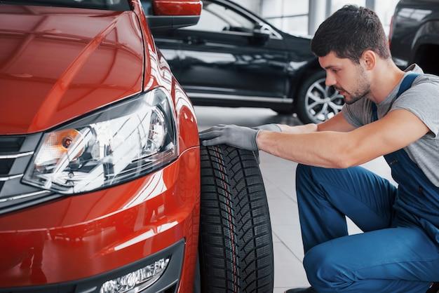 Mecânico com um pneu de ônibus em uma garagem de reparação. substituição de pneus de inverno e verão