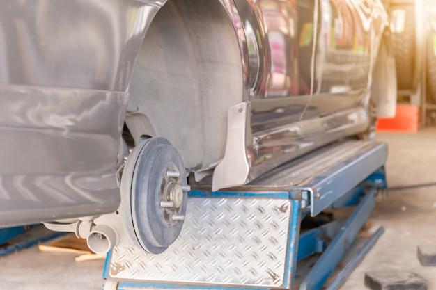 Mecânico consertando o dispositivo de alinhamento de roda em uma roda de carro de substituição de pneu novo