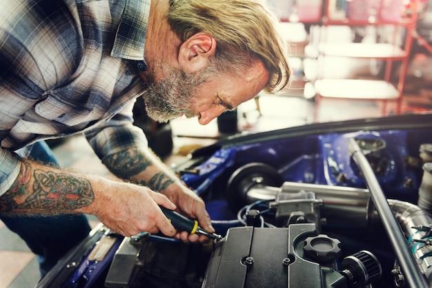 Mecânico da manutenção do motor da garagem que fixa o conceito de reposição