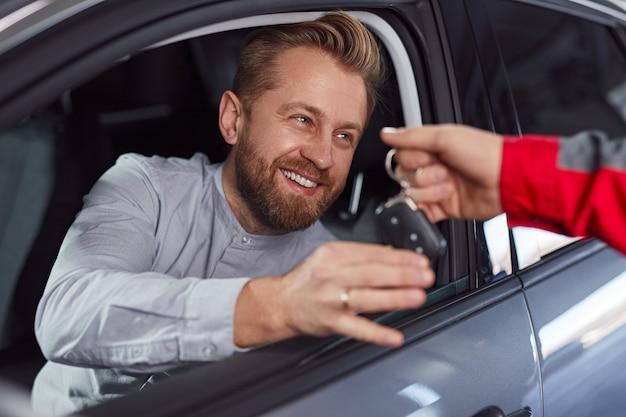 Mecânico dando as chaves do carro para cliente satisfeito no salão de serviços de conserto