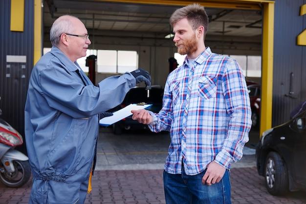 Mecânico dando as chaves do carro para um cliente