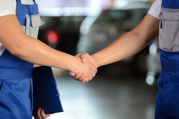 Mecânico de aperto de mão de dois homens no serviço de reparação automóvel