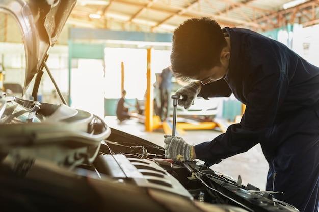 Mecânico de automóveis asiático homem usando uma chave inglesa e chave de fenda para trabalhar o carro de serviço na garagem.