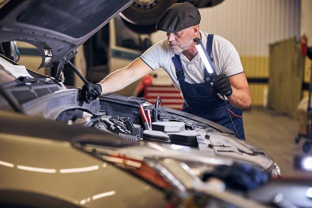 Mecânico de automóveis barbudo consertando carro em posto de gasolina