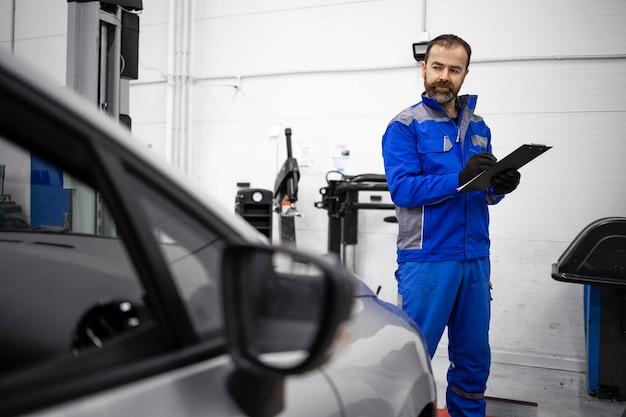 Mecânico de automóveis caucasiano barbudo de meia idade fazendo inspeção visual do veículo na oficina e segurando a lista de verificação.