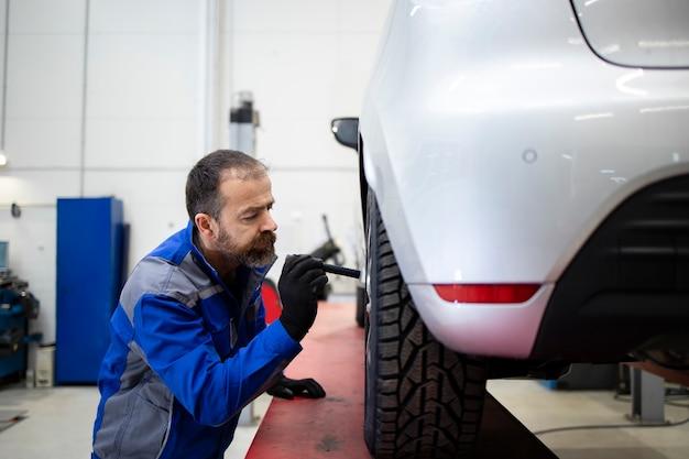 Mecânico de automóveis caucasiano barbudo de meia idade profissional fazendo inspeção visual das pastilhas e discos de freio.