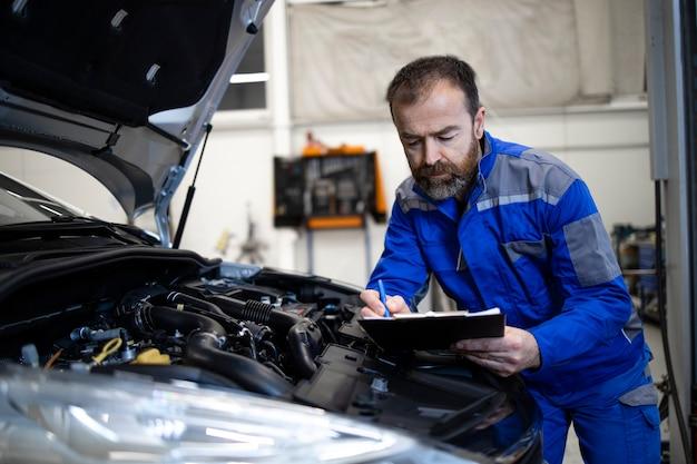 Mecânico de automóveis caucasiano de meia idade profissional com lista de verificação ao lado da área do motor do veículo com capô aberto, detectando mau funcionamento.