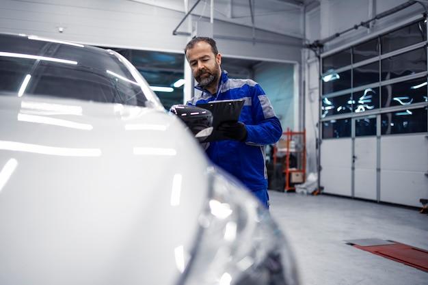 Mecânico de automóveis caucasiano de meia idade profissional fazendo inspeção visual do veículo na oficina e segurando a lista de verificação.