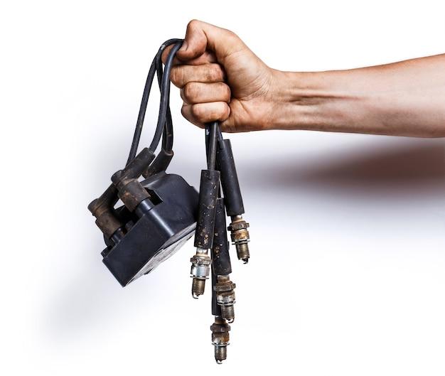 Mecânico de automóveis com fios antigos de alta tensão, velas e bobina de ignição
