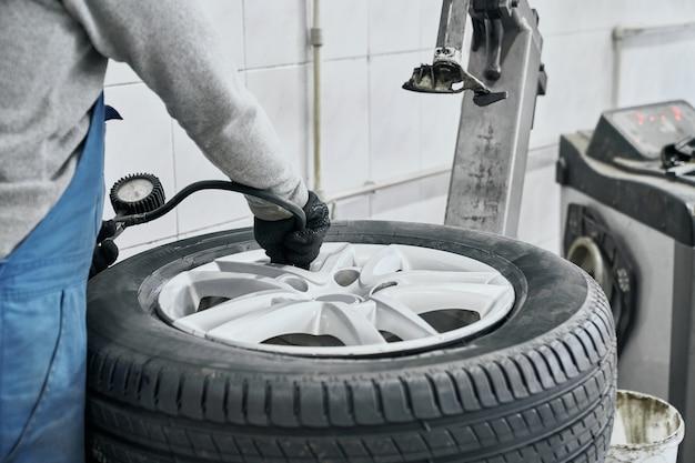 Mecânico de automóveis com suéter cinza e luvas pretas inflando pneu e verificando a pressão do ar com o manômetro na estação de serviço. conceito de medição e manutenção