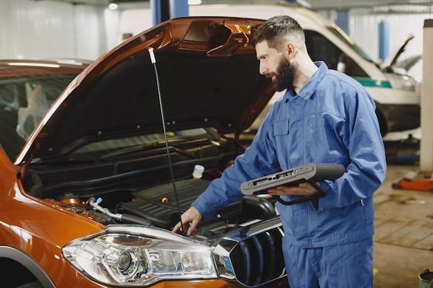 Mecânico de automóveis com um tablet perto de um carro com roupa de trabalho