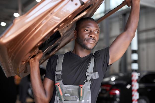 Mecânico de automóveis confiante segurando uma parte separada do carro