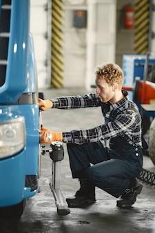 Mecânico de automóveis conserta carro na garagem com ferramentas