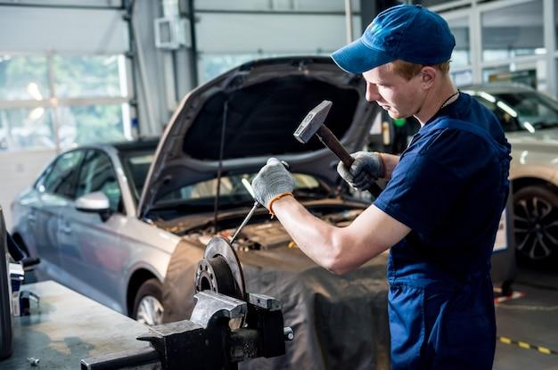 Mecânico de automóveis conserta freios de automóveis em estação de serviço