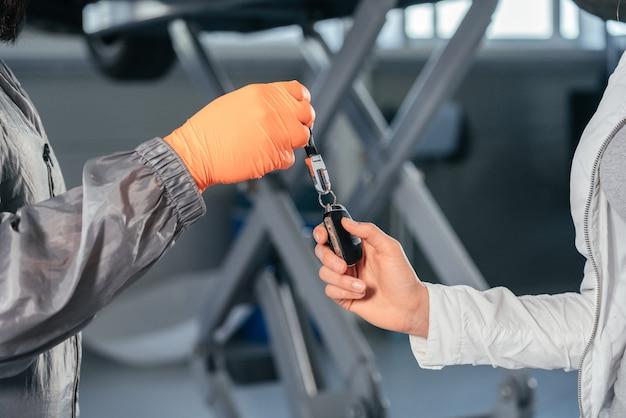 Mecânico de automóveis dando as chaves do carro para sua cliente na oficina em um centro de reparos de automóveis de qualidade