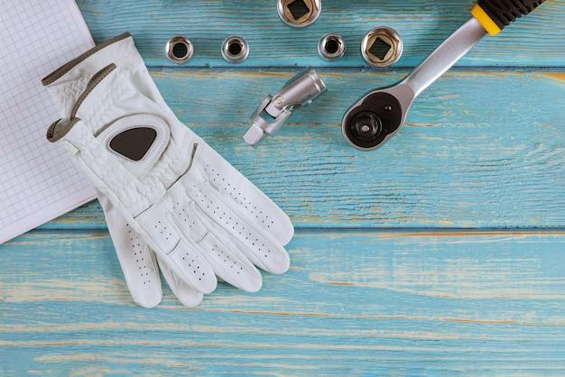 Mecânico de automóveis de reparação de automóveis para chaves combinadas, luvas de trabalho no automóvel de chave inglesa em um fundo de madeira
