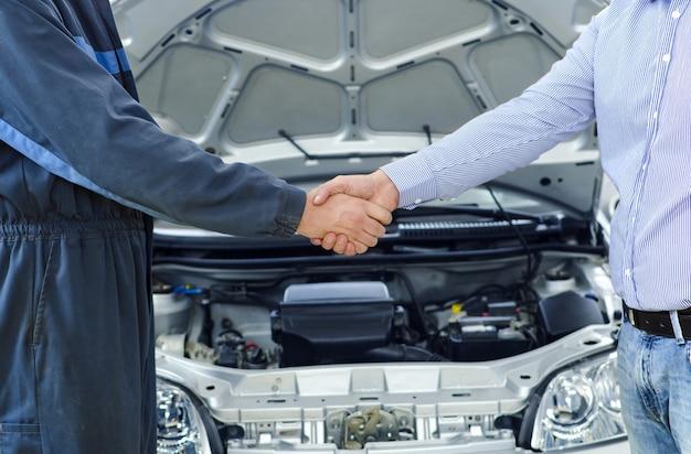 Mecânico de automóveis e cliente apertando as mãos na frente do veículo